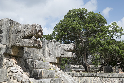 Feathered serpents at the stairs to a platform in the ancient Mayan city of Chichen Itza. Chichen Itza was a large pre-Columbian city built by the Maya people, located in Tinúm Municipality, Yucatán State, Mexico.