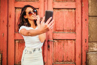 青年女人,自拍,彩色背景,肖像,红色背景,从容态度,现代,拿着,仅女人,仅一个女人