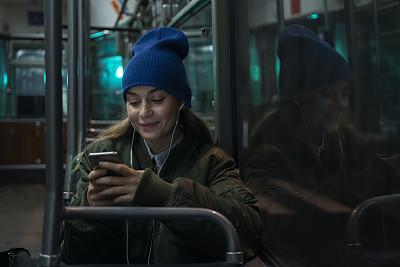 夜晚,在活动中,交通工具内部,商业金融和工业,拿着,仅女人,仅一个女人,乘客,看,耳机