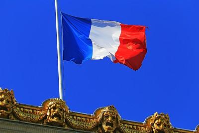 French flag waving against clear blue Sky – Paris, France