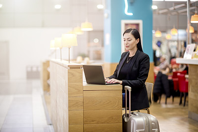 Young beautiful  woman working in airport café while waiting a flight