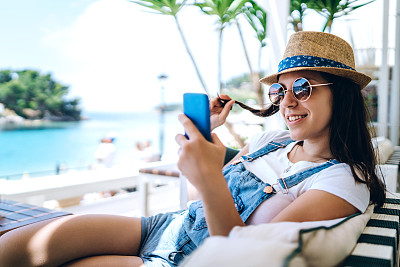 Young woman is using phone in beach café