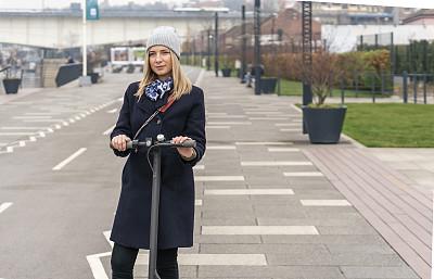 青年女人,电动滑板车,,30岁到34岁,现代,河流,全身像,欢乐,通勤者,户外,高峰时间