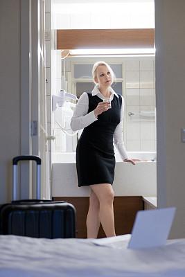 浴室,饮用水,女商人,酒店,垂直画幅,水,笔记本电脑,45到49岁,忙碌,饮料