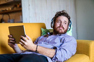 青年男人,沙发,入耳式耳机,电子阅读器,留白,半身像,电子邮件,洛杉矶县,30岁到34岁,美洲