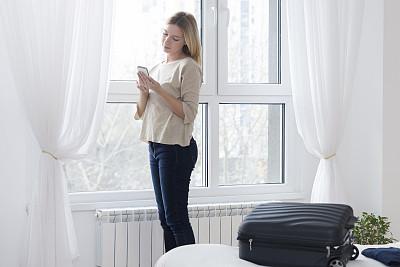 青年人,女商人,发短信,宾馆客房,手提箱,透过其它物体观看,行李,拆包,旅行者,周末活动