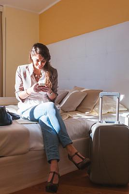 宾馆客房,女人,仅一个中老年女人,垂直画幅,笔记本电脑,电话机,行李,白人,仅成年人,青年人