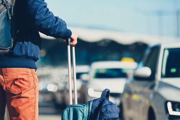 拉着行李箱在机场等车