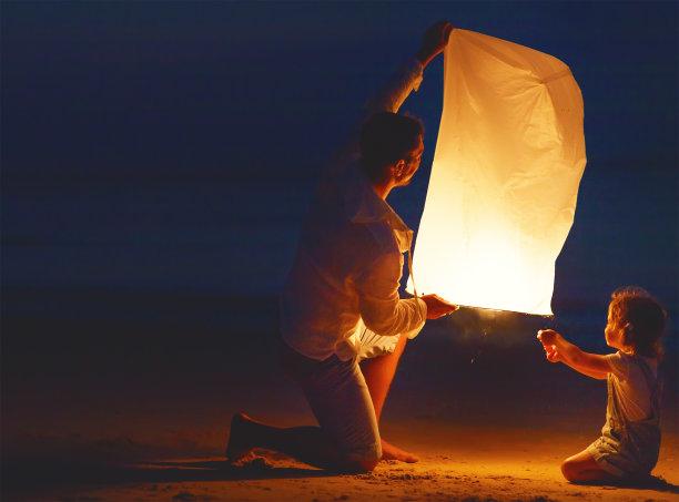 海滩上男人和孩子放灯笼