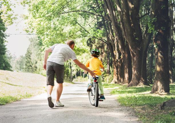 父亲指导孩子学习单车